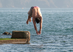 © under license to London News Pictures.  15/03/2011 A man dives in to the sea in Plymouth, Devon. Picture credit sould read: David Hedges/LNP
