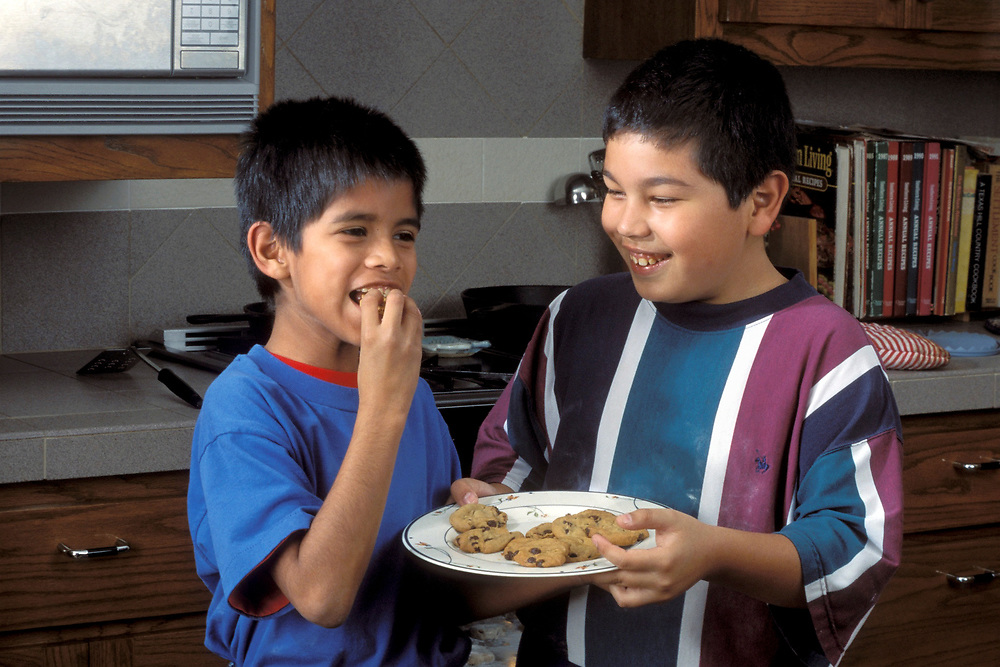 Two 10 year old Hispanic boys eating cookies after baking them.<br /> ©Bob Daemmrich/