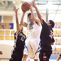 Zuni Thunderbird Ryan Bowekaty (25) grabs a rebounded ball between Crownpoint Eagles Darnell Cook (15) and Samuel Jeff (32) Tuesday night in Zuni.