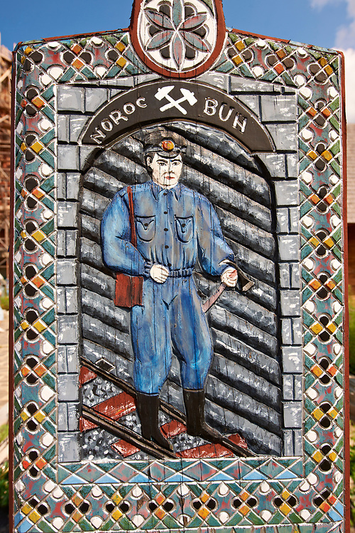 Tombstone of a miner,  The  Merry Cemetery ( Cimitirul Vesel ),  Săpânţa, Maramares, Northern Transylvania, Romania.  The naive folk art style of the tombstones created by woodcarver  Stan Ioan Pătraş (1909 - 1977) who created in his lifetime over 700 colourfully painted wooden tombstones with small relief portrait carvings of the deceased or with scenes depicting them at work or play or surprisingly showing the violent accident that killed them. Each tombstone has an inscription about the person, sometimes a light hearted  limerick in Romanian. .<br /> <br /> Visit our ROMANIA HISTORIC PLACXES PHOTO COLLECTIONS for more photos to download or buy as wall art prints https://funkystock.photoshelter.com/gallery-collection/Pictures-Images-of-Romania-Photos-of-Romanian-Historic-Landmark-Sites/C00001TITiQwAdS8