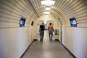 Two men walk along a secure walkway from their wing to the eduction centre inside HMP Featherstone, Wolverhampton, Staffordshire United Kingdom. HMP Featherstone is a Category C adult male training prison with a population of around 700 and operated by HM Prison Services. (Picture credit: © Andy Aitchison)