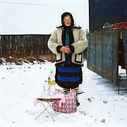 A Romanian peasant farmer sells home distilled horinca (plum brandy) at Ocna Sugatag market, Maramures, Romania. She is wearing a striped apron (zadie) made of a single width of woven wool with horizontal blue and black stripes, traditional footwear (opinci) worn with felt foot wraps (obiele) and a fleecy jacket (guba). Traditionally subsistence farmers In Maramures raise their own sheep to provide wool for knitting and weaving clothing.