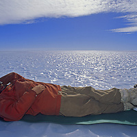 Queen Maud Land, Antarctica.A polar explorer takes a break, encircled by a vast, bare ice glacier.