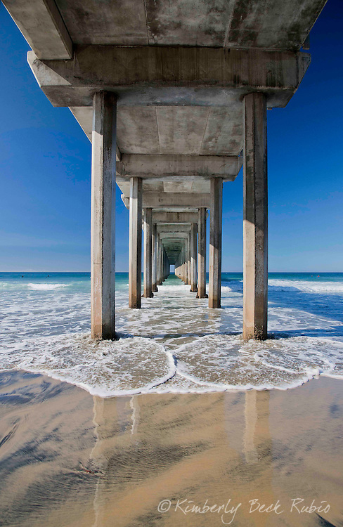 Diminishing perspetive looking through the blue green waters under Scripps Pier in La jolla, California, with the tide rushing in beneath.