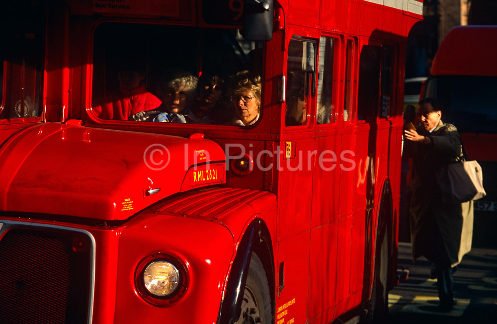 A red London bus is passing between sunlight and shadow as passengers sit patiently in heavy traffic on Piccadilly in Central London. At the back of the vehicle, a man is leaping on to the back to board via the entrance and exit, a characteristic of these old, classic modes of London transport. These buses are being fazed out in favour of more modern, cleaner fuel-burning vehicles where passengers can mount and dismount safer as many passengers injured themselves. The bus is a traditional design called a Routemaster which has been in service on the capital's roads since 1954 and is nowadays only seen on heritage and tourist routes. From any angle, the bus is easily recognisable as that classic British transport icon.
