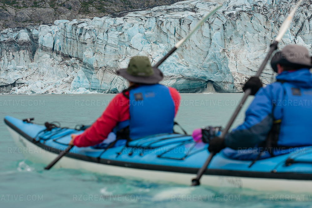 A couple paddles a tandem sea kayak in Glacier Bay National Park and Preserve with Lamplugh Glacier in the distance. Photo © Robert Zaleski / rzcreative.com<br /> —<br /> To license this image contact: robert@rzcreative.com