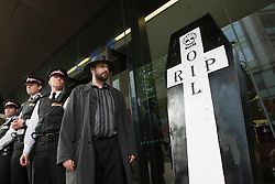© licensed to London News Pictures. London, UK 22/05/2012. Occupy London protesters leave a mock coffin outside Shell's AGM in Barbican today (22/05/12). Photo credit: Tolga Akmen/LNP