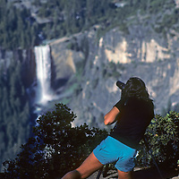 A hiker photographs Vernal Falls from Glacier Point in Yosemite National Park, California.