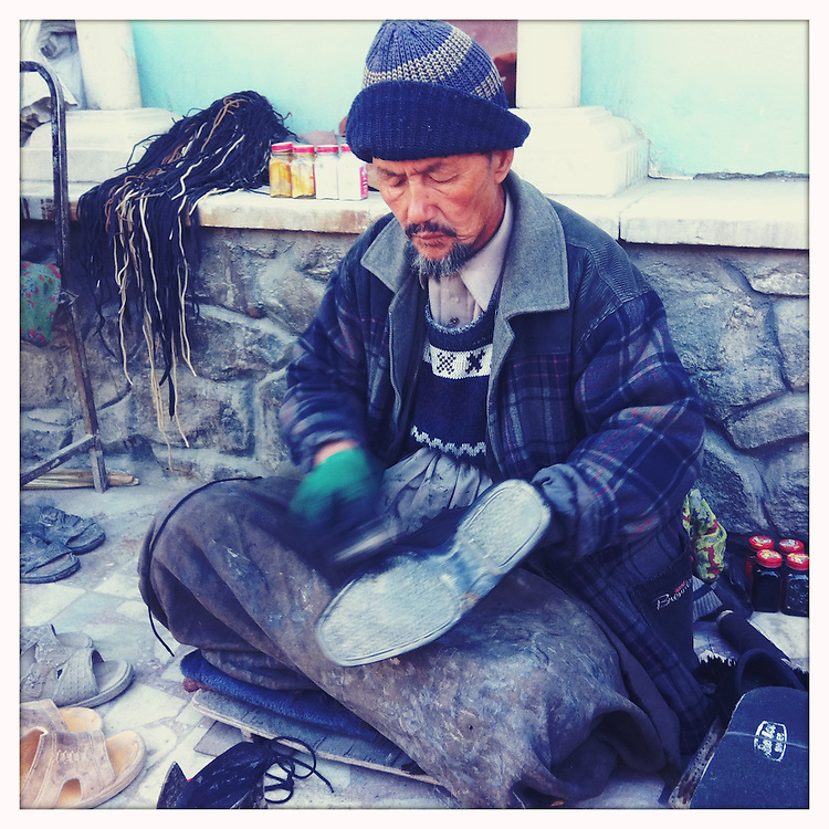 A man shines shoes in the Shar-e Now district of Kabul.