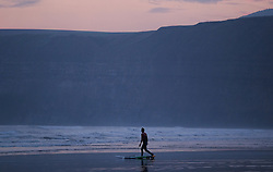 © Licensed to London News Pictures.28/10/15<br /> Saltburn, UK. <br /> <br /> A stand-up paddleboarder stretches before entering the water as the early morning light spreads over the cliffs and beach at Saltburn in Cleveland. <br /> <br /> Photo credit : Ian Forsyth/LNP