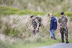 Defence Forces personnel assist Garda officers searching the Military Road area in the Wicklow Mountains after human remains believed to be from a murdered young man were found in the area.