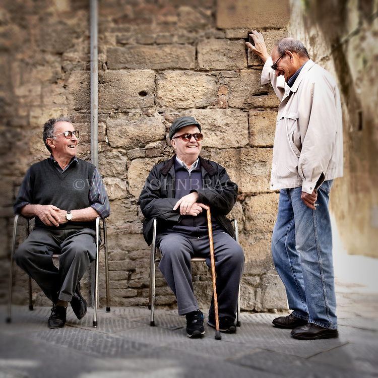 Three elderly Italian men laughing in Volterra, Italy.