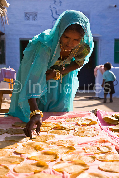An indian woman  turns over sun dried poppadoms she is making in here back yard, Salawas, Rajasthan, India.