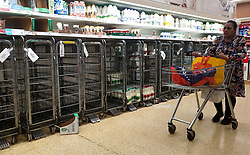 © Licensed to London News Pictures. 07/10/2021. London, UK. A shopper walks past empty shelves of fresh milk in Sainsbury's, north London just after 9am. The Government and retailers warn that food shortages could continue until Christmas due to labour shortages following Brexit. Photo credit: Dinendra Haria/LNP