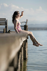Mature woman sitting in swimsuit on pier and looking at distance, Bavaria, Germany