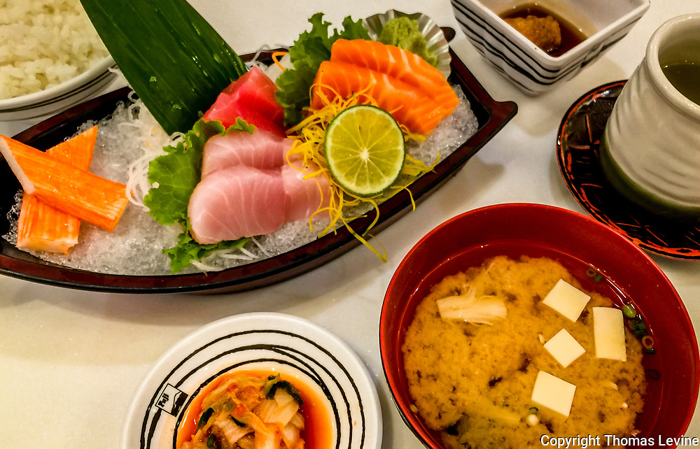 Japanese Sushi in a small boat served with Miso Soup, kimchi and soy sauce. Shot from high angle. Phuket, Patong, iPhone