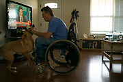 """BIRMINGHAM, AL – JUNE 13, 2015: Matthew Seals, 47, plays with his dog Max in his new home in the Winchester Hills neighborhood. <br /> <br /> In April 1998, a deadly F5 tornado ripped through the suburbs of Birmingham, Alabama, killing 32 people and destroying hundreds of homes. Seventeen years later, Matthew Seals is still learning to cope with the loss of his youngest son, who was killed in the storm. With help from Habitat for Humanity, Seals completed construction on a new home in 2015, where he continues to raise his remaining children and his new life as a paraplegic. Despite his own suffering from the tragedy, Seals volunteers with Habitat to help other families find their own form of stability through home ownership. """"Habitat gives you an opportunity to help yourself,"""" Seals said. """"Not just for the immediate need, but for the long term to become more self-sufficient, more self-confident, and more self-reliant."""""""