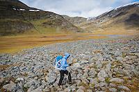 Female hiker hikes over rocky terrain in Tjäktjavagge on Kungsleden trail, Lappland, Sweden