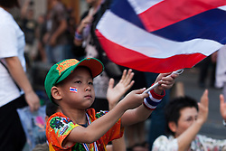 © Licensed to London News Pictures. 05/01/2014. A Young Boy waves the Thai flag at a Rally during the third day of the 'Bangkok Shutdown' as anti-government protesters continue with their 'shutdown' of Bangkok.  Major intersections in the heart of the city have been blocked in their campaign to oust Prime Minister Yingluck Shinawatra and her government in Bangkok, Thailand. Photo credit : Asanka Brendon Ratnayake/LNP