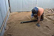 Marty checks the levelness of the cistern's sand pad.