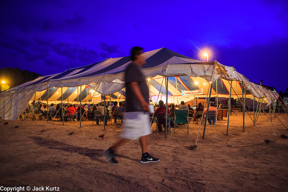"""12 JULY 2012 - FT DEFIANCE, AZ:  A man walks past the main tent at the 23rd annual Navajo Nation Camp Meeting in Ft. Defiance, north of Window Rock, AZ, on the Navajo reservation. Preachers from across the Navajo Nation, and the western US, come to Navajo Nation Camp Meeting to preach an evangelical form of Christianity. Evangelical Christians make up a growing part of the reservation - there are now more than a hundred camp meetings and tent revivals on the reservation every year. The camp meeting in Ft. Defiance draws nearly 200 people each night of its six day run. Many of the attendees convert to evangelical Christianity from traditional Navajo beliefs, Catholicism or Mormonism. """"Camp meetings"""" are a form of Protestant Christian religious services originating in Britain and once common in rural parts of the United States. People would travel a great distance to a particular site to camp out, listen to itinerant preachers, and pray. This suited the rural life, before cars and highways were common, because rural areas often lacked traditional churches.    PHOTO BY JACK KURTZ"""