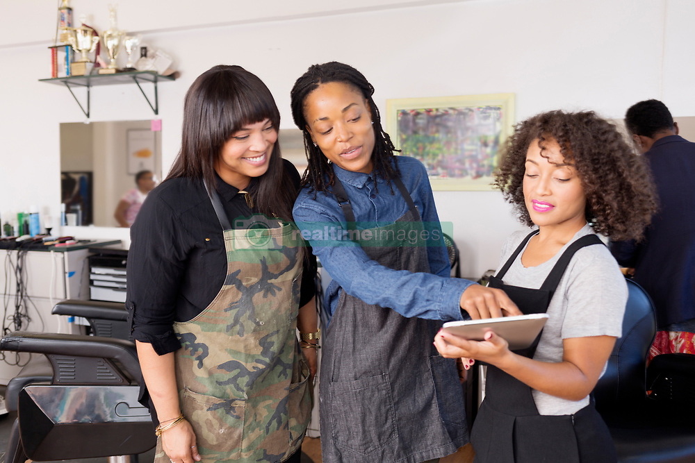 September 10, 2016 - Ca, CA - Female barbers pointing at digital tablet in team meeting in barber shop (Credit Image: © Alyson Aliano/Image Source via ZUMA Press)