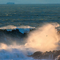 Heavy surf waves roll ashore from the Pacific Ocean at Gray Whale Cove State Beach near Montara, California. Behind, a container ship carries goods to a port in San Francisco Bay.