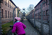 A young visitor taking photographs of the  barbed wire fence which is surrounding the Auschwitz Nazi concentration camp. It is estimated that between 1.1 and 1.5 million Jews, Poles, Roma and others were killed in Auschwitz during the Holocaust in between 1940-1945.