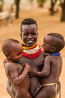 A girl of the Kara tribe holds two toddlers, Dus village, above the Omo River, Omo Valley, Ethiopia.