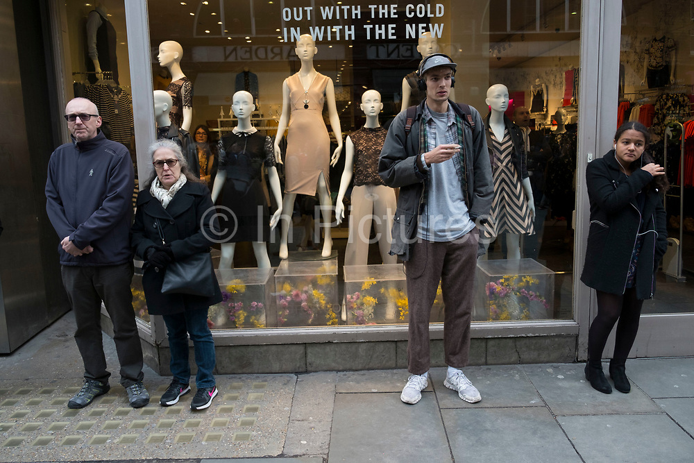 People and shop window display mannequins interacting in London, England, United Kingdom.