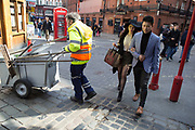 Stylish Asian couple walk past a street sweeper in Soho, London, UK.
