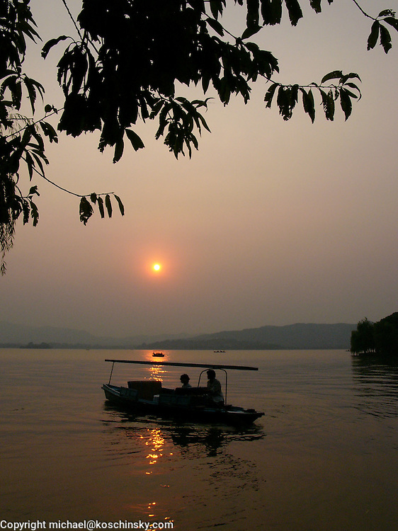 Chinese Rowing Boat setting out in the sunset, West Lake, Hangzhou