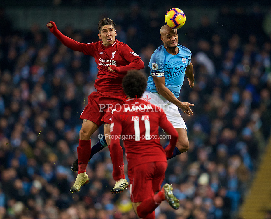 MANCHESTER, ENGLAND - Thursday, January 3, 2019: Liverpool's Roberto Firmino (L) and Manchester City's captain Vincent Kompany during the FA Premier League match between Manchester City FC and Liverpool FC at the Etihad Stadium. (Pic by David Rawcliffe/Propaganda)
