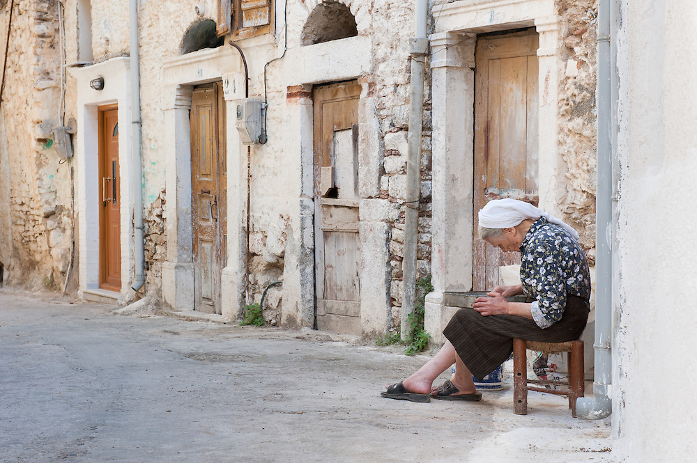 """An elderly woman clearing the mastic drops in the medieval village of Pyrgi, Chios, Greece.  The resin of the tree fells on a layer of sand. Once the sand is cleared the solidified mastic drop has to be cleared manually from foreign bodies, chunks of the trunk and small pebbles. <br /> <br /> Pyrgi in Chios is known as the """"painted village"""" on account of the decoration of the houses. The village still keeps its medieval style and together with the other Mastichochoria (Mastic Villages) are in the list of the Intangible Cultural Heritage of Humanity of UNESCO"""