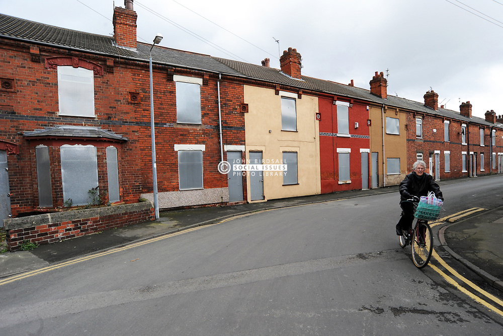 A woman cycles past rundown housing, Goole near Hull