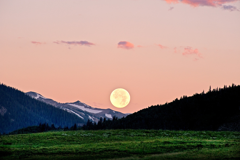 """Much to my dismay, the full moon was obscured by clouds in the """"perfect"""" location I'd chosen for the rise over Crested Butte, Colorado. Planning to shoot sunrise, I set my alarm for 5:30. After a night of fitful sleep, I awoke around 4:30 to a bright light shining through a small crack in the curtain directly over the foot of my bed. As I reached my hand to close the curtain, there she was .. the full moon descending. What a sight to behold as I opened the curtain, lay back on the bed and watched (not particularly photo worthy) for several minutes until she hid behind Mt. Crested Butte. Attempting sleep was futile, so I decided to get ready and head out a bit earlier than planned. On my way to photograph a field of lupine in the early morning light, I glanced westward and there she was again in all her glory. Close to moon set, I quickly crossed two lanes and pulled onto the shoulder. Two cameras, two tripods and feeling like the luckiest woman in the world, I got my shot. And it was even better than I'd hoped for. Had she not awakened me at 4:30, I would have missed this splendid moment. Had I not received her gentle nudgings, I would have missed this splendid moment. And in the midst of this moment, I heard Leonard singing low ... """"Ring the bells that still can ring. Forget your perfect offering. There is a crack in everything. That's how the light gets in ..."""""""