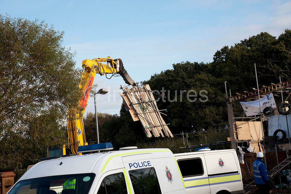 Heavy machinery starts to remove the scaffolding gantry. Travellers at Dale Farm site prior to eviction. Riot police and bailiffs were present on 20th October 2011, as the site was cleared of the last protesters chained to barricades. Dale Farm is part of a Romany Gypsy and Irish Traveller site in Crays Hill, Essex, UK<br /> <br /> Dale Farm housed over 1,000 people, the largest Traveller concentration in the UK. The whole of the site is owned by residents and is located within the Green Belt. It is in two parts: in one, residents constructed buildings with planning permission to do so; in the other, residents were refused planning permission due to the green belt policy, and built on the site anyway.
