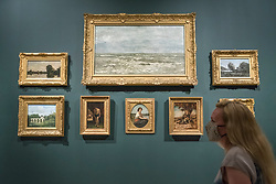 """© Licensed to London News Pictures. 04/08/2020. LONDON, UK. A staff member poses with works by Delacroix and Corot in a recreation of a display at Ordrupgaard. Preview of """"Gauguin and the Impressionists : Masterpieces from the Ordrupgaard Collection"""" at the Royal Academy of Arts in Piccadilly.  60 works from a collection of Impressionist paintings, assembled by wealthy Danish couple Wilhelm and Henny Hansen, are on show 7 August to 18 October 2020, and includes masterpieces by Gauguin, Degas, Monet, Morisot, Pissarro, Renoir and Sisley.  Photo credit: Stephen Chung/LNP"""