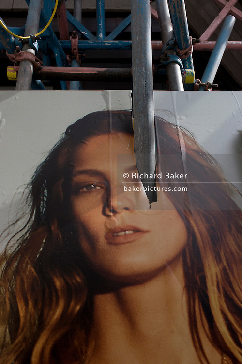 Woman model's poster face pierced by vertical scaffolding pole in central London.
