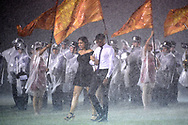 Members of the Celebration Homecoming Court walk on the field during a downpour during halftime of a high school football game against Saint Cloud in Celebration, Fla., Friday, Oct. 2, 2015. (Phelan M. Ebenhack)
