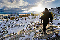 A woman walking across rocks at sunrise in the upper Enchantments, Enchantment Lakes Wilderness Area, Washington Cascades, USA.