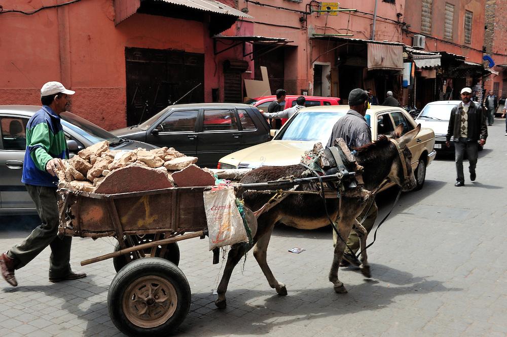 Work men steer a donkey carting rubble through the medina in Marrakesh