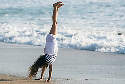 A young girl doing a handstand on Fistral Beach in Newquay, Cornwall.