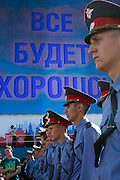 """Moscow, Russia, 12/06/2010..Police in Red Square stand under a giant display covering Lenin's mausoleum and reading """"Everything Will Be Alright"""" at a concert to mark the Russia Day national holiday."""