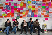 Men sit and rest in front of a wall plastered with ads offering services in jewelry fabrication at the China Commodities City in Yiwu, Zhejiang Province, China on 06 March  2013. The city of Yiwu is known as one of China's largest trading centers for small merchandise and light industry, drawing buyers from around the world. Uncertain global demand, a stronger yuan currency and rising labour costs have taken their toll on Chinese exporters, but analysts believe sales could pick up modestly in 2014 due to improved demand from the United States and Europe.