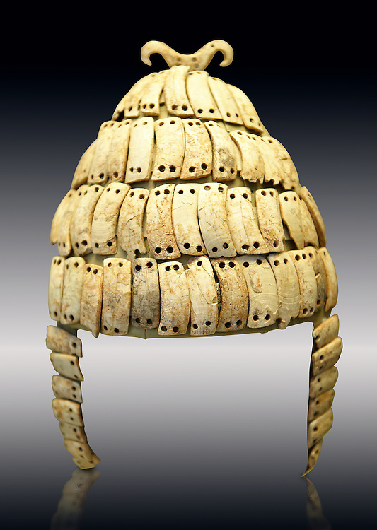 """Boar's tusk helmet with cheek guards and double bone hook on top. Tomb 515 Mycenae, Greece. 14th-15th century BC. National Archaeological Museum, Athens.. The Boar's tusk helmet was described in the Iliad as follows """"Meriones gave Odysseus a bow, a quiver and a sword, and put a cleverly made leather helmet on his head. On the inside there was a strong lining on interwoven straps, onto which a felt cap had been sewn in. The outside was cleverly adorned all around with rows of white tusks from a shiny-toothed boar, the tusks running in alternate directions in each row..?Homer, Iliad 10.260-5"""" .<br /> <br /> If you prefer to buy from our ALAMY PHOTO LIBRARY  Collection visit : https://www.alamy.com/portfolio/paul-williams-funkystock/mycenaean-art-artefacts.html . Type -   Athens    - into the LOWER SEARCH WITHIN GALLERY box. Refine search by adding background colour, place, museum etc<br /> <br /> Visit our MYCENAEN ART PHOTO COLLECTIONS for more photos to download  as wall art prints https://funkystock.photoshelter.com/gallery-collection/Pictures-Images-of-Ancient-Mycenaean-Art-Artefacts-Archaeology-Sites/C0000xRC5WLQcbhQ"""