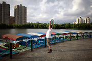 A retired pensioner raises his hands up to excercise while standing in a park in Shanghai, China on 04 August, 2011.