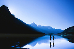 North America, Canada, Alberta, father and son fishing in lake below mountains