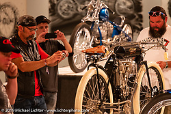 "Guests check out the 1908 Indian Twin ""Torpedo Tank"" 61 cubic inch board track racer from the Jill and John Parham Collection at the National Motorcycle Museum on view in the What's the Skinny Exhibition (2019 iteration of the Motorcycles as Art annual series) at the Sturgis Buffalo Chip during the Sturgis Black Hills Motorcycle Rally. SD, USA. Thursday, August 8, 2019. Photography ©2019 Michael Lichter."