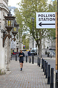 People walk beside a sign of a polling station in central London on Wednesday, May 5, 2021. The 2021 London mayoral election will be held on 6 May 2021 to elect the mayor of London. The mayoral and Assembly elections were originally due to be held on 7 May 2020, but in March 2020 the government announced the election would be postponed until 2021 due to the COVID-19 pandemic. (Photo/ Vudi Xhymshiti)